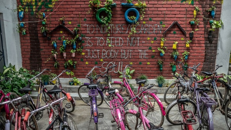 "Around ten colorful bikes are parked in front of a red brick wall with plants hanging from the wall. On the wall in white capital letters is written:""To nurture a garden is to feed not just body but the soul."" The wal lis deorated with plants in colorful tires or pots."